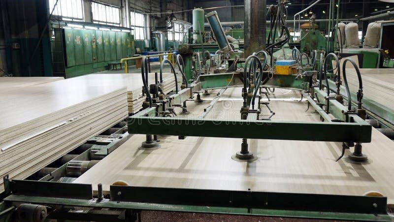 Produktion av den pl?terade tr?fiberplattan Fibreboardark f?r m?blemangproduktion royaltyfri bild
