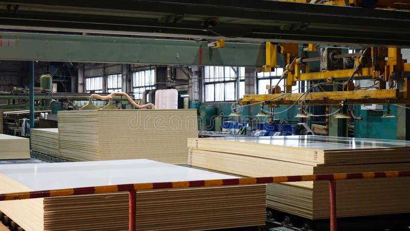 Produktion av den pl?terade tr?fiberplattan Fibreboardark f?r m?blemangproduktion arkivbild