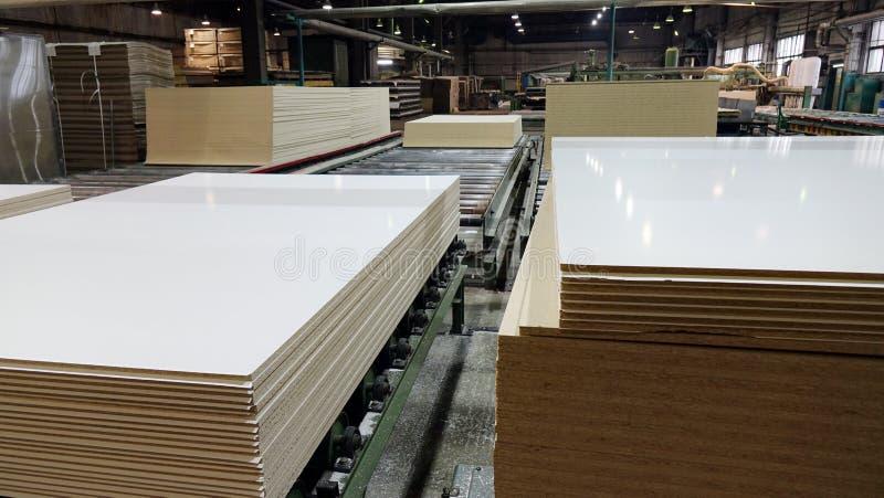 Produktion av den pl?terade tr?fiberplattan Fibreboardark f?r m?blemangproduktion arkivfoton