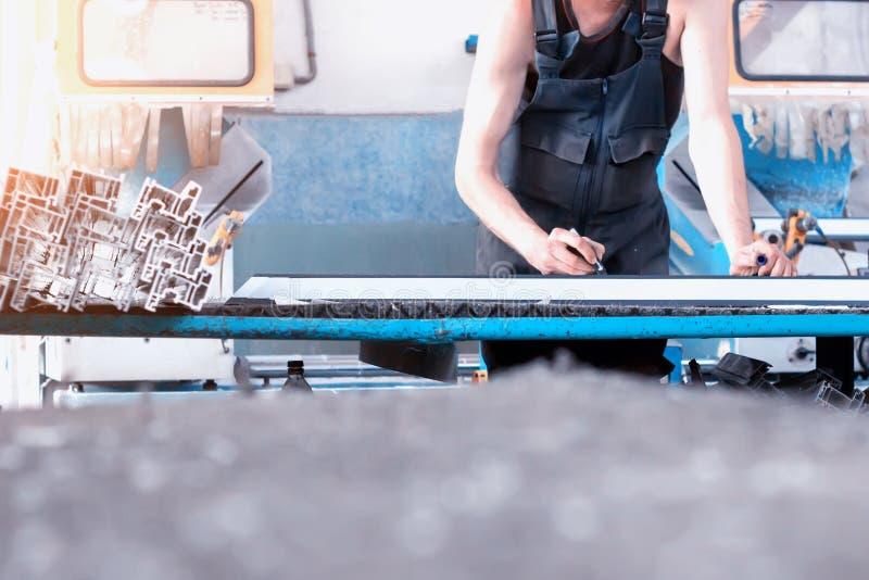 Produktion av PVC-fönster, arbetaren antecknar mått på profilen av rampvcen, filtpennarm arkivfoto