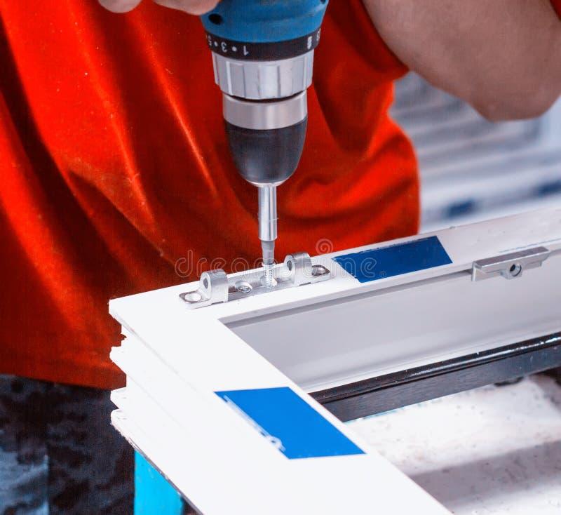 Produktion av pvc-fönster, arbetaren skruvas med en skruvmejsel med ett knäpp till pvc-fönstret, närbilden, skruvmejsel arkivbild