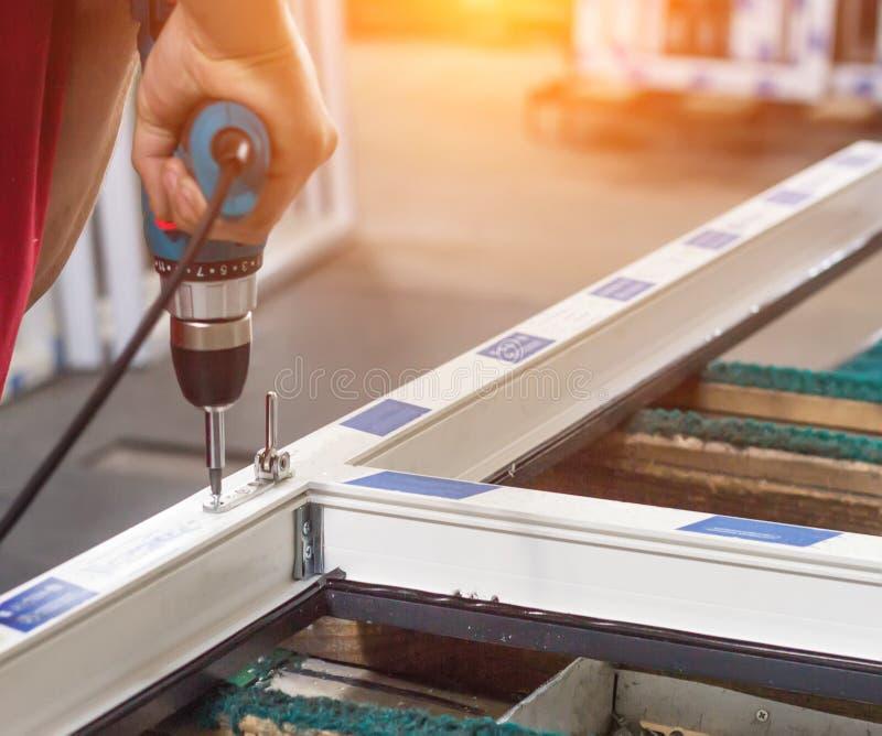 Produktion av pvc-fönster, arbetaren skruvas med en skruvmejsel med ett knäpp till pvc-fönstret, närbilden, skruvmejsel royaltyfria foton
