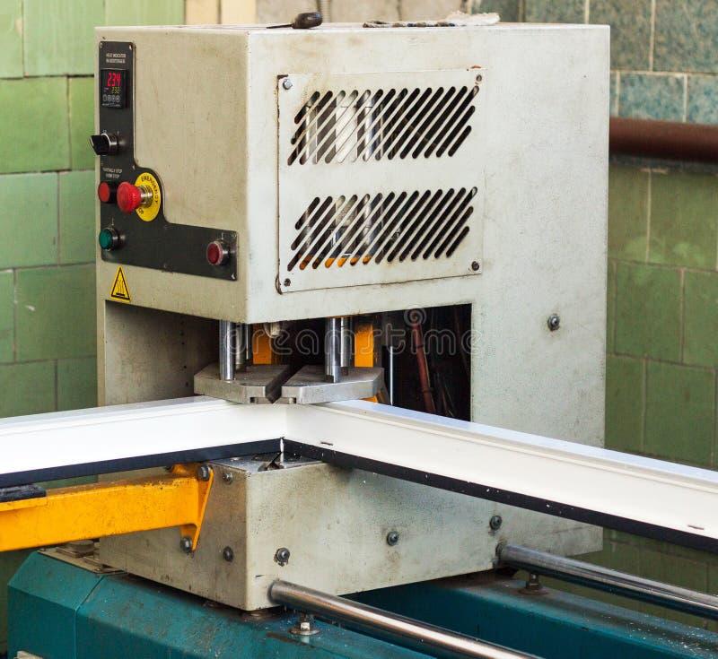 Produktion av pvc-fönster, att limma av plast- hörn av fönster, bearbetar med maskin för tillverkning av pvc-fönster, profil royaltyfri fotografi