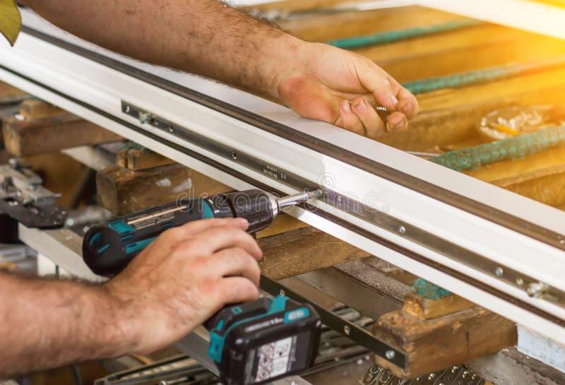 Produktion av pvc-fönster, en man skruvar en skruvmejsel in i ett pvc-fönster, närbilden, fönsterpvc arkivbild