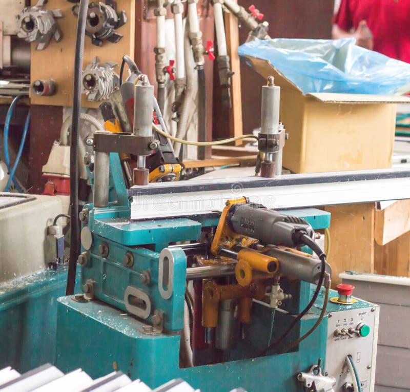 Produktion av PVC-fönster, en maskin för att borra hål i rampvcen, drillborrhjälpmedel arkivbild