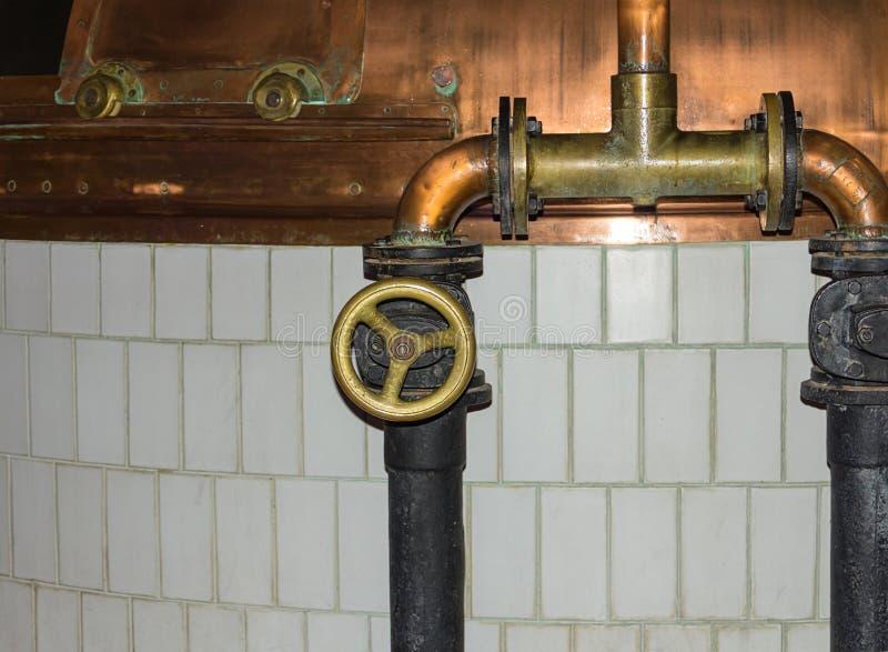 Produktion des alten Systems des Bieres der Rohre mit Ventilfüllung von kupfernen Bottichen für das Kochen stockbilder