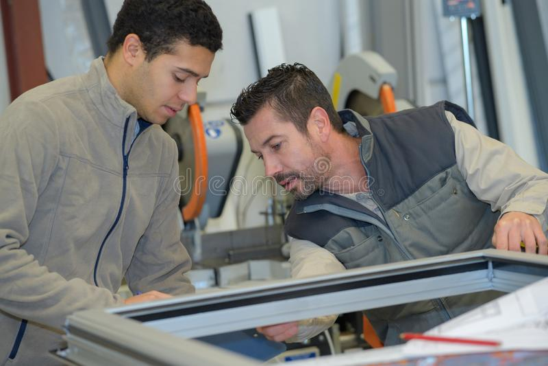 Produktion som ler arbetare i overall med det olika PVC-fönstret fotografering för bildbyråer