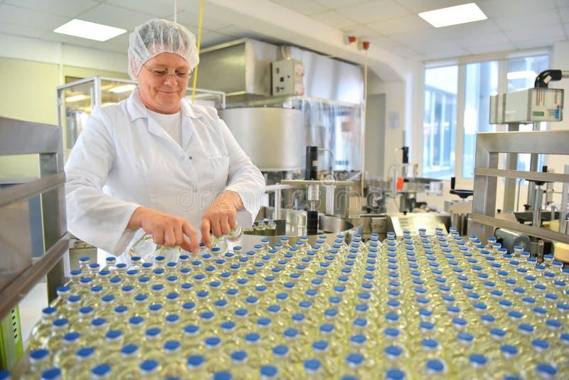 Produktion und Füllen von Drogen in einem pharmazeutischen Fördererbel stockfotografie