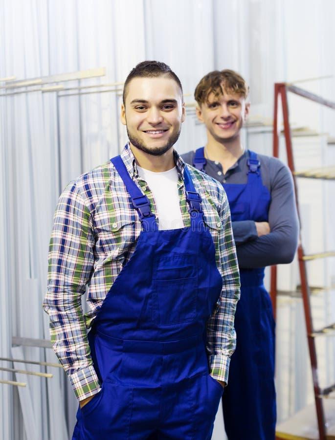 Produktionarbetare i overaller med fönsterprofiler royaltyfria bilder
