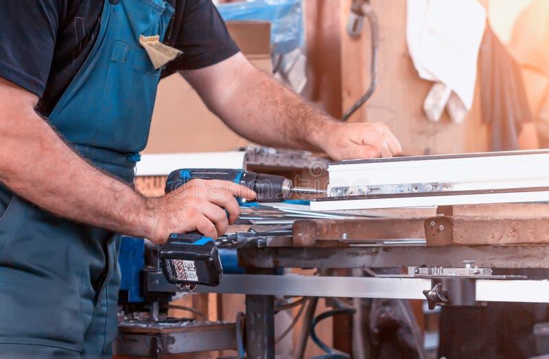 Produktionfönster pvc, man skruvade skruvmejseln försett med gångjärn försvar på fönsterrampvc-ramen, närbilden, arbete arkivfoto