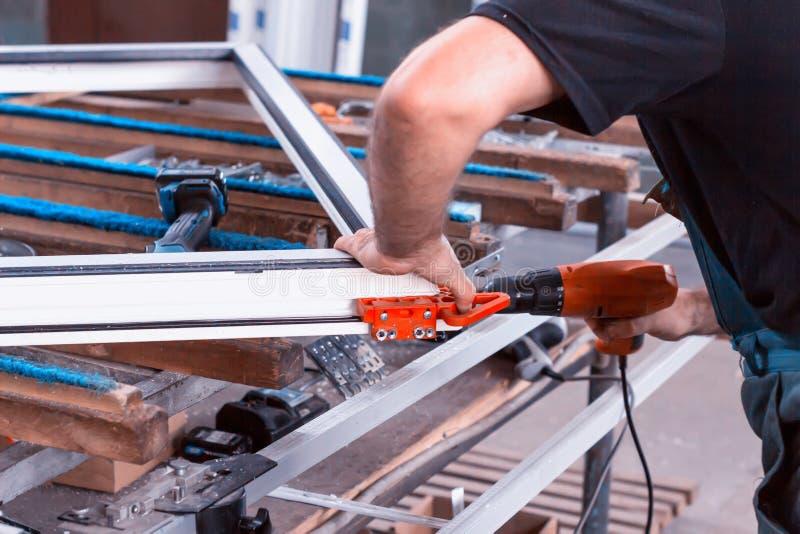 Produktionfönster pvc, man skruvade skruvmejseln försett med gångjärn försvar på fönsterrampvc-ramen, närbilden, arbete, process arkivbilder