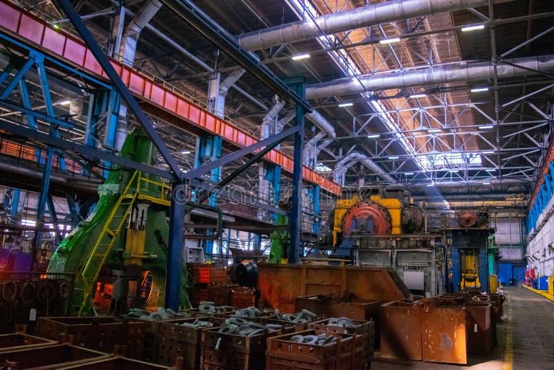 Produktionmaskiner, utrustning och tungt järn som stämplar i det industriellt, shoppar smedjaväxten royaltyfria bilder