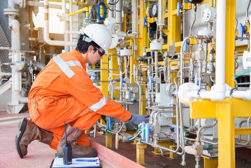 Produktionoperatören justerar flödeshastighet av pumpen för korrosionsinhibitoren som panelmankommando vid radion och rekord- dat royaltyfria bilder