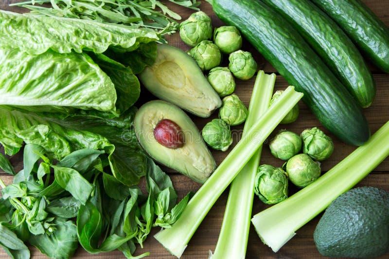 Produkty zawiera folic kwas - B9 witamina Zieleni warzywa na drewnianym tle Seler, arugula, avocado, Bruksela zdjęcia royalty free