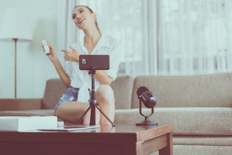 Produto bonito dos cosméticos da revisão e da demonstração do blogger da mulher na tela da câmera do telefone celular imagens de stock royalty free