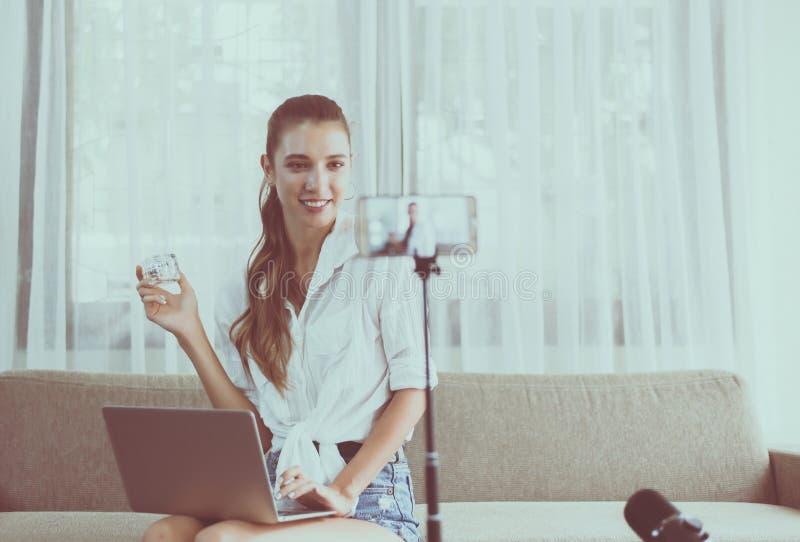Produto caucasiano bonito novo dos cosméticos da revisão e da demonstração do blogger da mulher na tela da câmera do telefone cel foto de stock