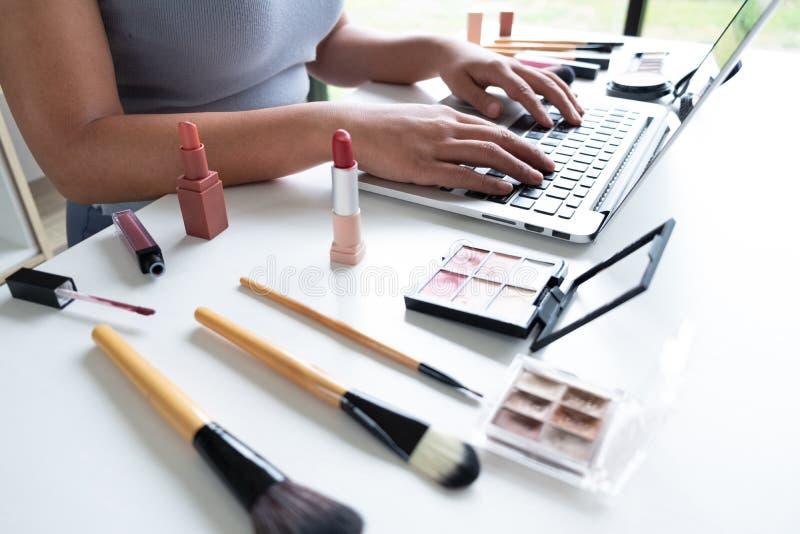Produto cosmético atual do blogger da mulher que senta-se na tabuleta dianteira e na transmissão à rede social pelo Internet, blo imagens de stock