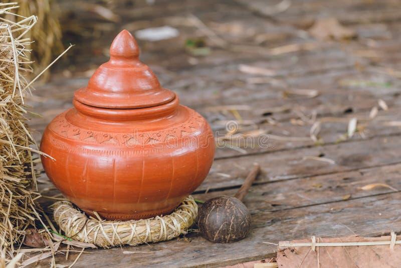 Produto de cerâmica antigo tailandês do potenciômetro de argila na casa do estilo antigo para o convidado foto de stock