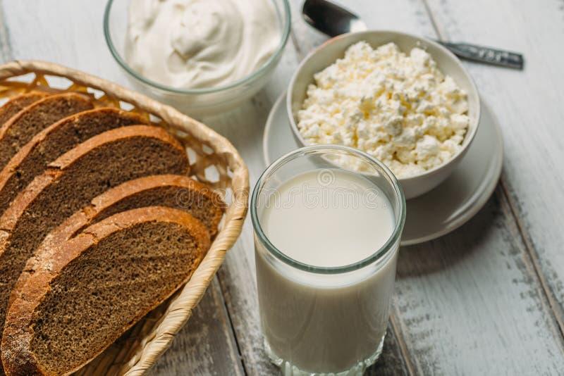 Produtos agrícolas rurais da leiteria em uma tabela de madeira: ordenhe em um vidro, requeijão, creme de leite foto de stock