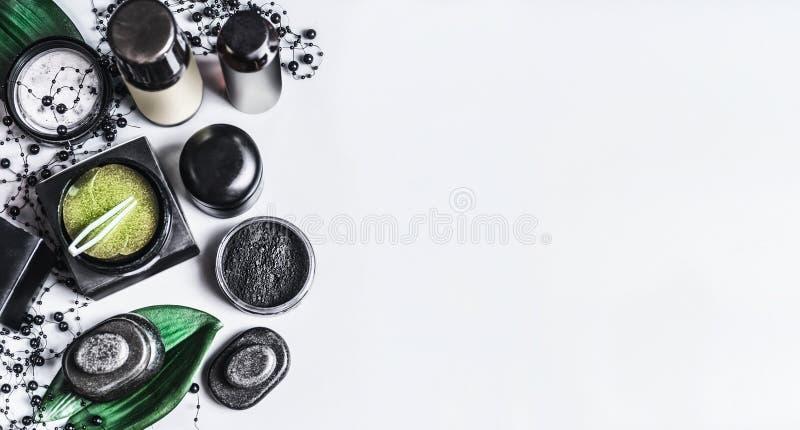Produtos cosméticos naturais pretos e verdes com os remendos do pó do carvão vegetal e do olho verde Grupo cosmético do carvão ve fotografia de stock