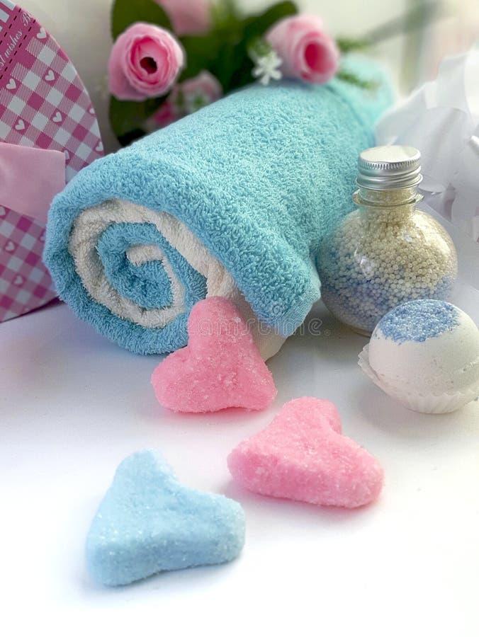 produtos cosm?ticos feitos a m?o dos termas as toalhas, sab?o, frasco do creme, esfregam a forma do cora??o no fundo branco imagens de stock