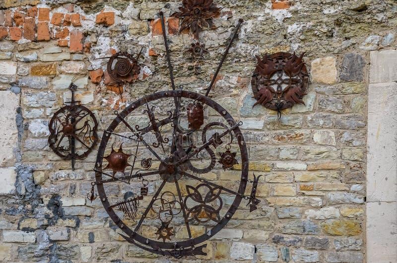 Produtos de cobre forjados em uma parede de pedra textured imagens de stock royalty free