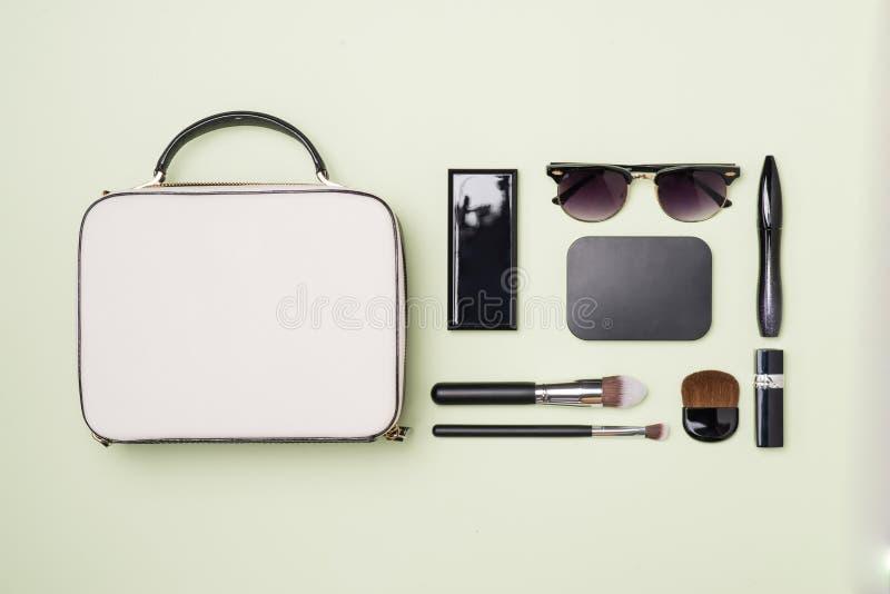 Produtos de composição com o saco cosmético no fundo da cor foto de stock royalty free
