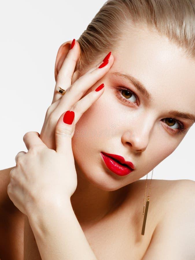Produtos de composi??o Menina bonita nova com brincos e anel do ouro que sorri no fundo branco Pregos vermelhos com tratamento de imagem de stock