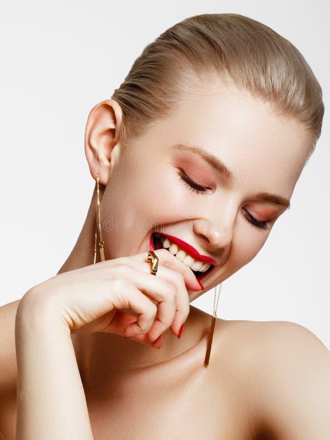 Produtos de composi??o Menina bonita nova com brincos e anel do ouro que sorri no fundo branco Pregos vermelhos com tratamento de imagem de stock royalty free