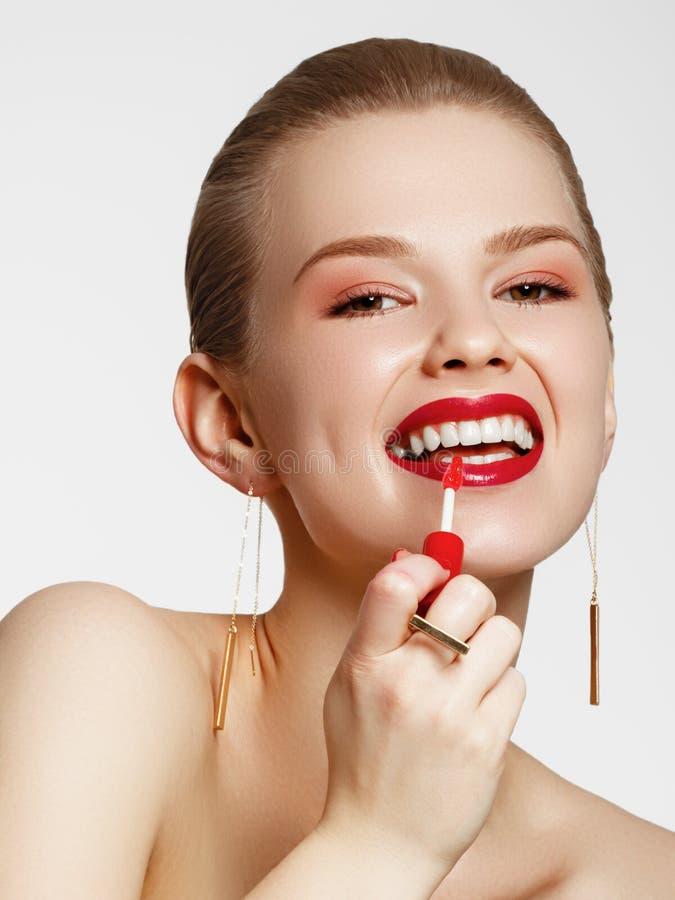 Produtos de composi??o Menina bonita nova com brincos e anel do ouro que sorri no fundo branco Pregos vermelhos com tratamento de fotos de stock
