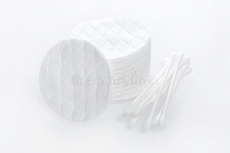 Produtos de higiene, almofadas de algodão e botões no fundo branco imagem de stock