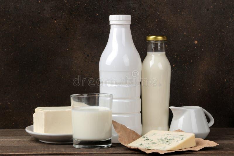 Produtos de leite leite, creme de leite, queijo, manteiga e requeijão em uma tabela de madeira marrom imagem de stock