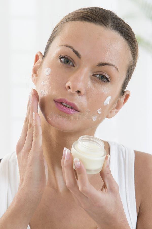 Produtos de Skincare - mulheres bonitas que aplicam o creme hidratante imagem de stock