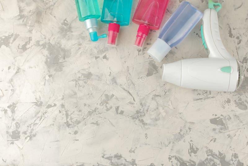 Produtos diferentes dos cuidados capilares e vários acessórios do cabelo e secadores de cabelo Em um fundo claro Cosméticos do ca imagens de stock