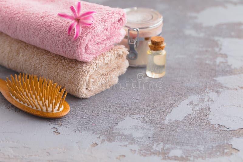 Produtos do óleo e da nata do cuidado do corpo dos termas com a escova e as toalhas de bambu orgânicas de cabelo imagens de stock royalty free