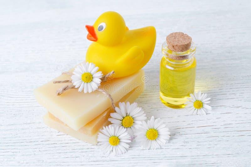 Produtos do cuidado do bebê, barra do sabão, óleo da massagem e flores frescas da camomila imagens de stock royalty free