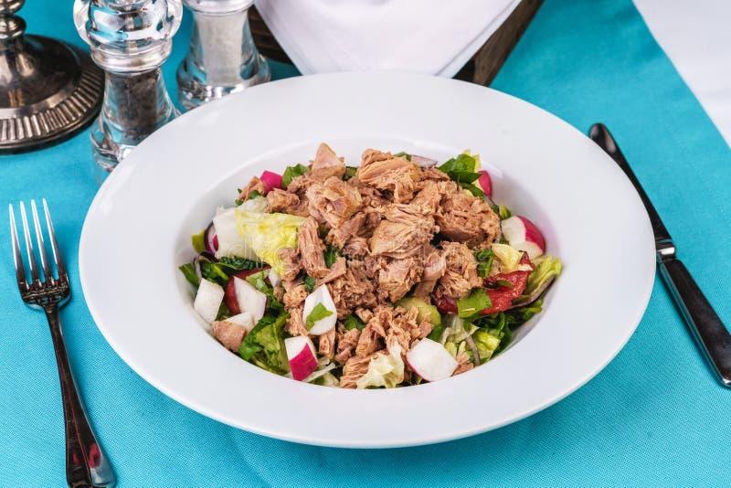 Produtos do mar, cozinha mediterrânica. Salada de atum do mar com verduras, pepinos, limão e pimenta-do-mar, rabanete. Alimento  imagens de stock royalty free