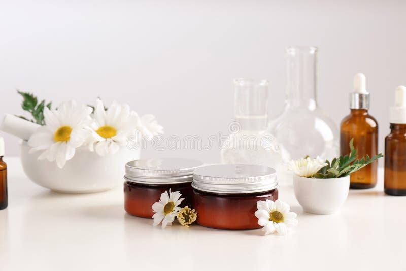 Produtos dos cuidados com a pele, ingredientes e produtos vidreiros de laboratório na tabela imagens de stock royalty free