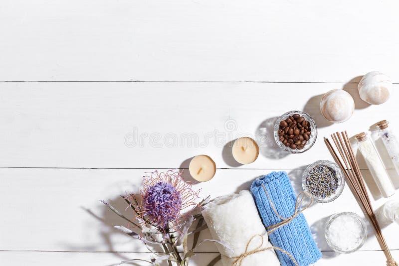 Produtos dos termas Sais de banho, flores secas alfazema, sabão, velas e toalha Configuração lisa no fundo de madeira branco, vis fotos de stock