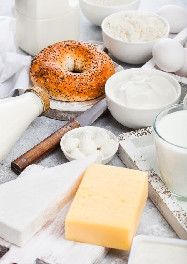 Produtos láteos frescos na caixa de madeira do vintage no fundo branco da tabela Frasco e vidro do leite, a bacia de creme de lei imagem de stock
