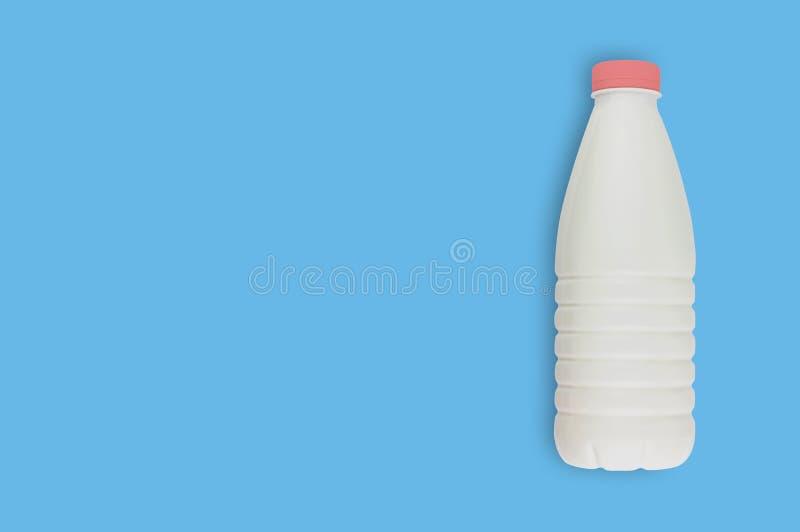 Produtos láteos frescos na garrafa plástica completa para o leite, o kefir ou o iogurte com o tampão vermelho na tabela azul na c foto de stock