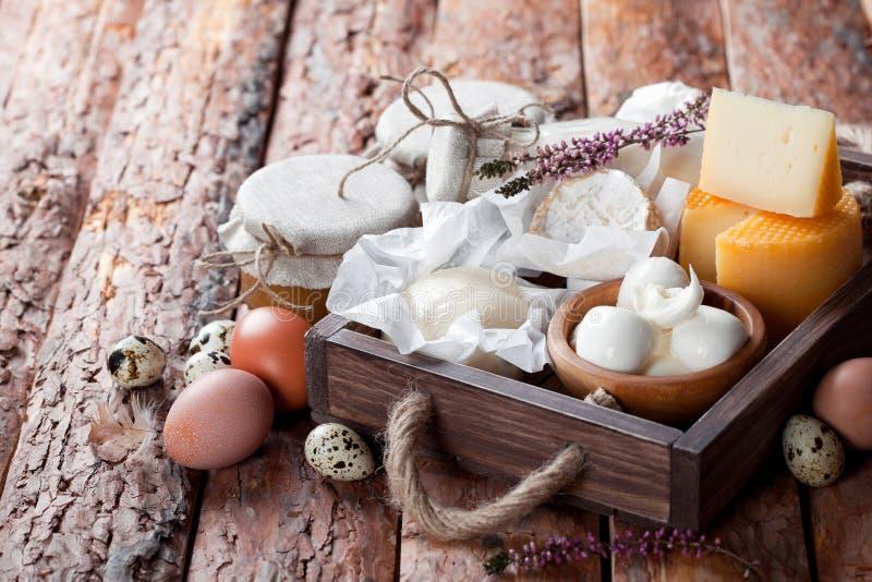 Produtos láteos frescos: queijo, manteiga, leite e ovos na caixa de madeira imagens de stock royalty free