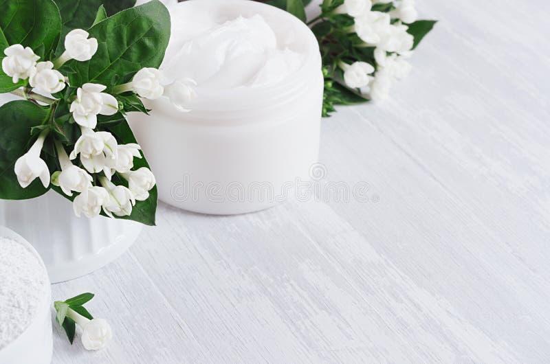 Produtos orgânicos dos cosméticos dos termas da mola fresca com as flores brancas e as folhas pequenas do verde no fundo de madei fotos de stock