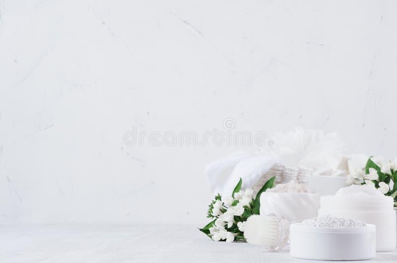 Produtos orgânicos dos cosméticos dos termas da mola fresca com as flores brancas e as folhas pequenas do verde no fundo de madei imagens de stock
