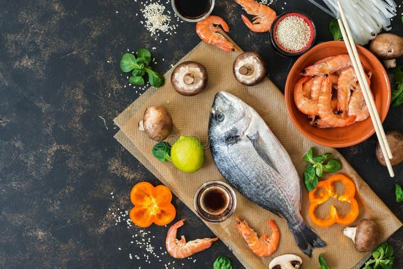 Produtos para cozinhar Culinária asiática e culinária mediterrânea Peixes, camarão, cogumelos Vista superior, espaço da cópia fotografia de stock