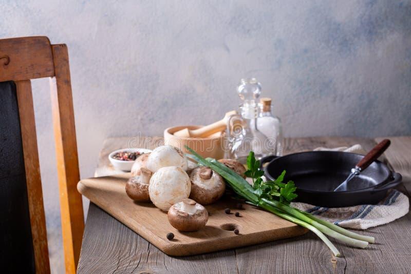 Produtos para a preparação de pratos em cogumelos Campeões, cebolas verdes sobre uma mesa de madeira Conceito de cozedura imagens de stock royalty free