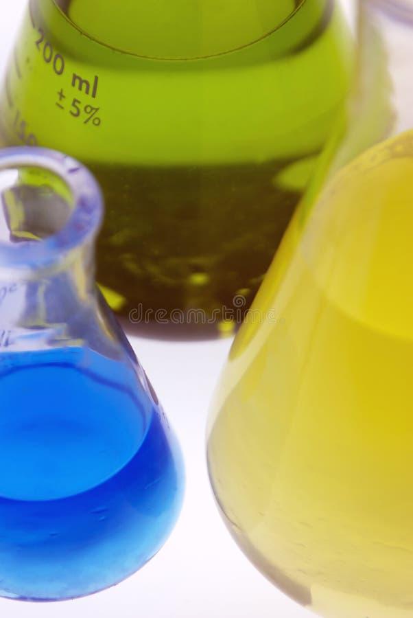 Produtos químicos azuis, amarelos e verdes em umas garrafas fotografia de stock