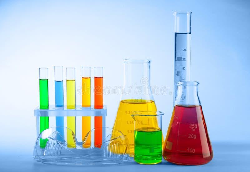 Produtos vidreiros de laboratório com líquidos coloridos e vidros protetores no fundo claro foto de stock
