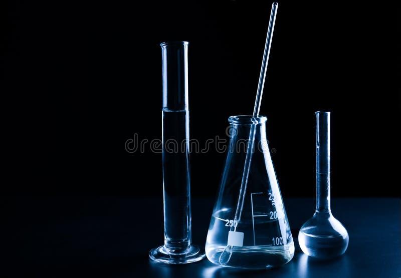 Produtos vidreiros de laboratório diferentes com líquido no fundo preto imagem de stock royalty free
