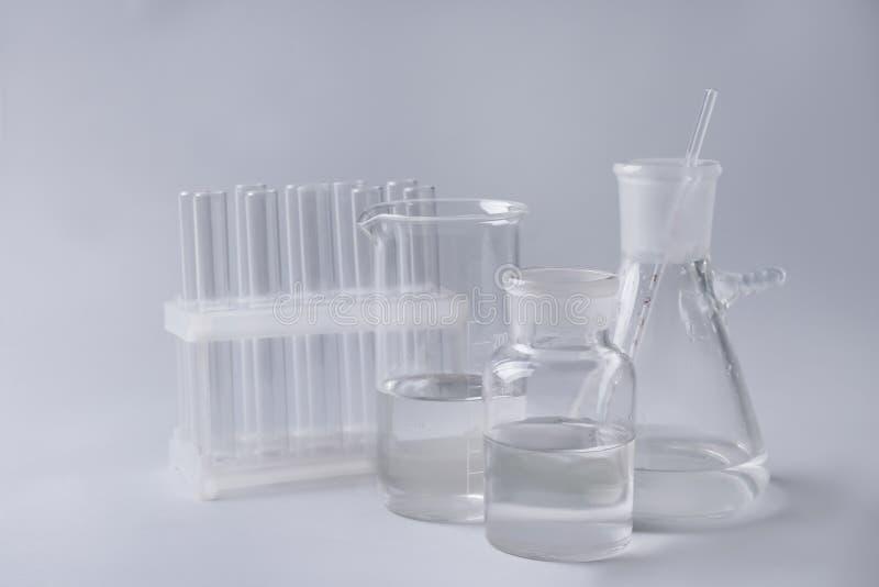 Produtos vidreiros de laboratório diferentes no fundo cinzento foto de stock